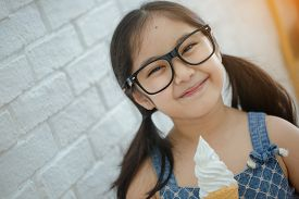 Happy Asian girl enjoy eating soft ice-cream