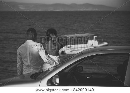 Sexy Couple. Couple In Love Stand Near Silver Car, Sea On Background. Couple Arrived On Vacation, Ho