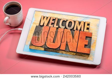 Welcome June banner - word abstract in vintage letterpress wood type on a digital tablet with a cup of coffee