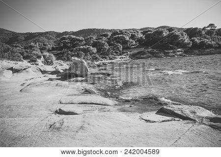 Rocky Beach Of Sea, Clear, Transparent Water Near Big Stone, Rock. Nature Landscape On Sunny Summer