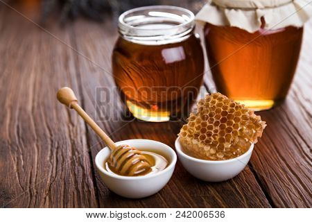 Honey in the comb, glass jar on wooden background