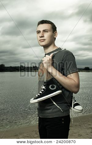 Portrait Of Young Man Standing On The River Bank With Trainers