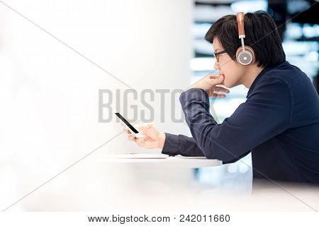 Young Asian Business Man Listening To Music By Headphones While Working With Laptop Computer In Co W