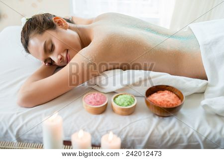 Young Beautiful Asian Woman Relaxing In The Spa Massage And Having Salt Scrub Massage At Back. Healt