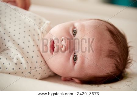 Close Up Of Newborn Baby Boy Lying On Changing Table In Nursery
