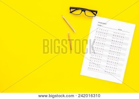 Exam Sheet On Yellow Table Top View Copy Space. Education Concept. Exam Problems. Broken Pencil Near