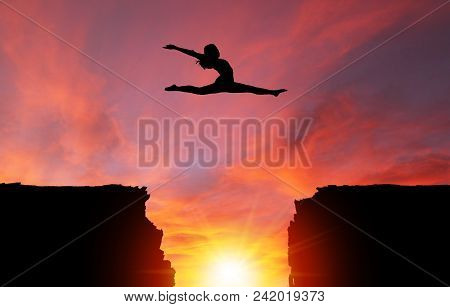 Silhouette Of Girl Dancer In A Split Leap Over Dangerous Cliffs With Dramatic Sunset Or Sunrise Back