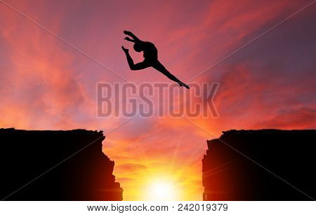 Silhouette Of Girl Dancer In A Stag Split Leap Over Dangerous Cliffs With Dramatic Sunset Or Sunrise