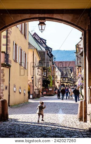 Riquewihr, France - April 27, 2017 : Girl Running Walking In Street With Half-timbered Houses On A S