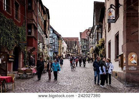 Riquewihr, France - April 27, 2017 : People Walking In Street With Half-timbered Houses On A Sunny D
