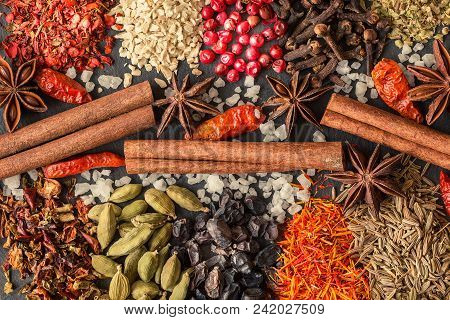 Aromatic Indian Spices On A Gray Slate Background. Herb And Spice Ingredients On Slate. Top View. Fo