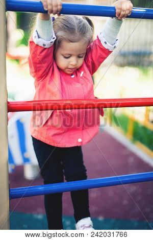 Climbing Little Girl At Playground. Playground Outdoor In Summer Time