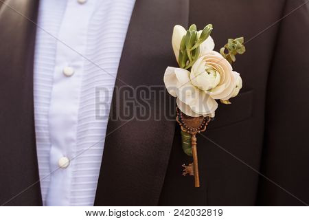 Close Up Photo Of Beautiful Boutonniere Decorated With Key On The Groom's Black Jacket. Soft Focus O