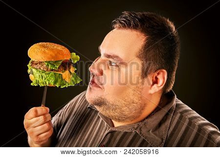 Man eating fast food. Overweight person eating huge hamburger on fork. People not going to lose weight. Challenge to society. Man suffers from gluttony. Obesity is harmful to health.