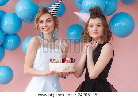 Two Young Girls Holding Birthday Cake And Show Very Excited Emotion.