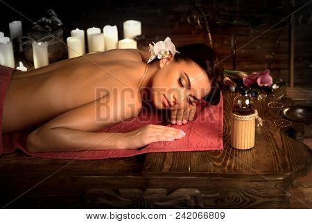 Massage of woman in spa salon. Girl on candles background in therapy room. Luxary interior in oriental therapy salon. Female have relax after sport. Spot light effect.