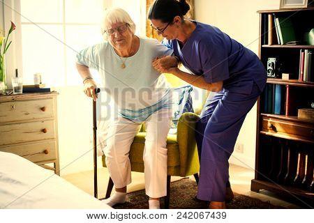 Nurse helping senior woman to stand up