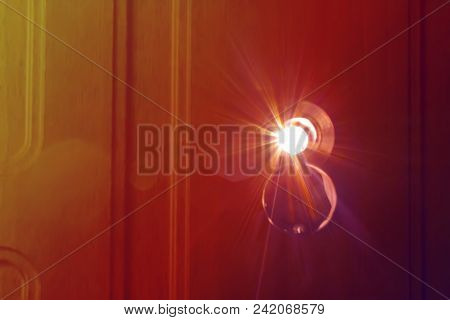The Bright Beam Of The Sun Shines Directly In A Door Peephole. A Beautiful Patch Of Light With Yello