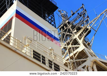Russian Naval Ship on Dock with Russian Flag Painted on Outdoor Deck. Navy Marine Ship Detail, Russian Icebreaker Cargo Ship against Blue Sky Backgorund. poster