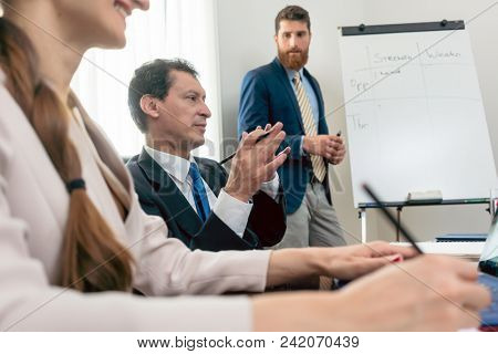 Reliable expert wearing formal business suit while conducting a SWOT analysis during board of directors meeting in the conference room of a successful company