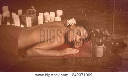 Massage of woman in spa salon. Girl on candles background in therapy room. Luxary interior in oriental therapy salon. Female have relax after sport with brown sepia and effect old fhoto.