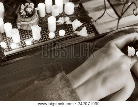 Massage of woman in spa salon. Girl on candles background in therapy room. Luxary interior in oriental therapy salon. Female have relax after sport. Black and white top view of photo.