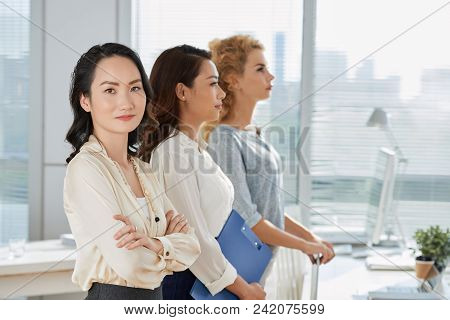Portrait Of Cheerful Chienese Business Lady With Coworkers Attending Training
