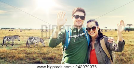 travel, hiking, backpacking, tourism and people concept - happy couple with backpacks waving hands over african savannah and zebras background