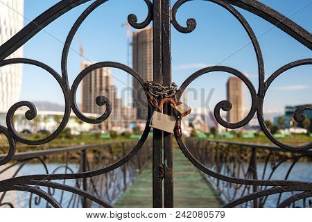 Locked Gate With Chain And Lock, Blurred Cityscape Background