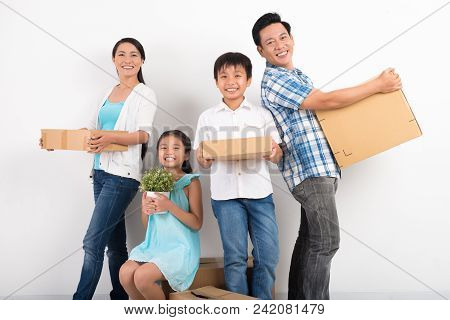Portrait Of Asian Family Standing With Boxes And Smiling At Camera