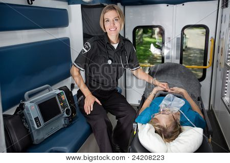 Female EMT professional in ambulance with senior woman patient