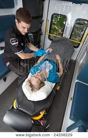 Ambulance professional with senior woman on stretcher