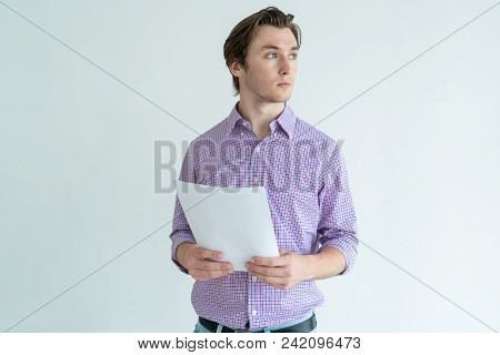 Pensive Young Man Holding Sheet Of Paper And Looking Away. Contemplation Concept. Isolated Front Vie
