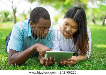 Serious Multiethnic Couple Or Friends Using Digital Tablet In Park. African American Man And Asian W
