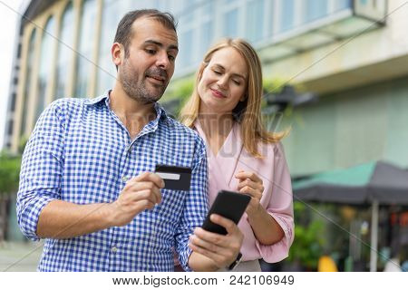 Confident Mid Adult Man Showing How To Pay In Online Shop With Credit Card To His Wife. Caucasian Co