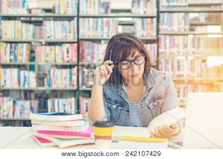 Asian Women In Library Reading And Thinking Something In A Book In A Library.  Education  Concept