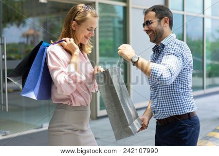 Smiling Mid Adult Man Showing His Purchase To Young Woman. Caucasian Couple Standing At Shop With Sh