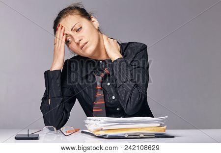 Headache. Office Woman Sitting At The Table. She Has A Headache