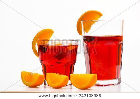 Bar Menu Concept. Glasses With Orange Drink Near Juicy Orange Fruit On White Background, Close Up. D