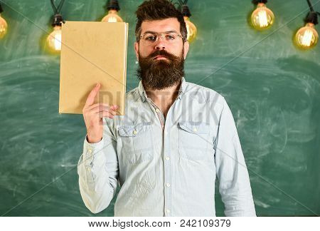 Teacher In Eyeglasses Holds Book In Hand, Copy Space. Man With Beard And Mustache On Calm Face Stand