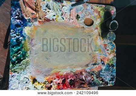 The Palette With Oil Paints Lies Next To The Canvas. Room Artist. Artist's Workshop.