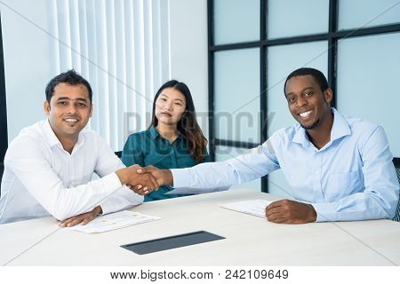 Cheerful Successful Interracial Business Partners Shaking Hands And Looking At Camera. Optimistic Co