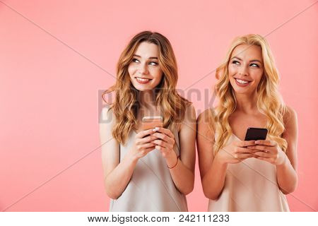 Two Pensive pleased pretty women in pajamas using smartphones and looking away over pink background