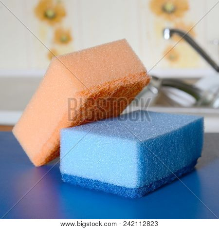 A Few Sponges Lie On The Background Of The Sink With Dirty Dishes