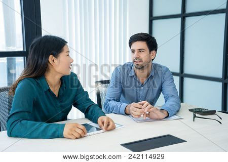 Two Serious Coworkers Talking At Conference Table. Caucasian Male And Asian Female Employees Waiting