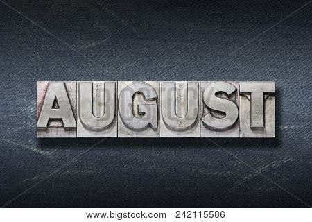 August Word Made From Metallic Letterpress On Dark Jeans Background