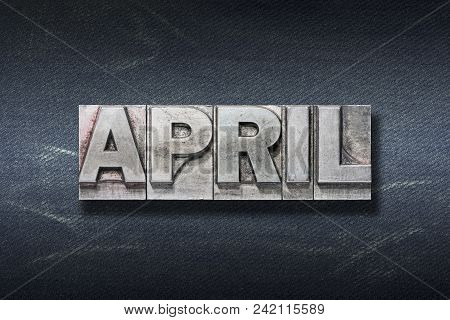 April Word Made From Metallic Letterpress On Dark Jeans Background