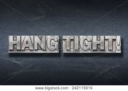 Hang Tight Phrase Made From Metallic Letterpress On Dark Jeans Background