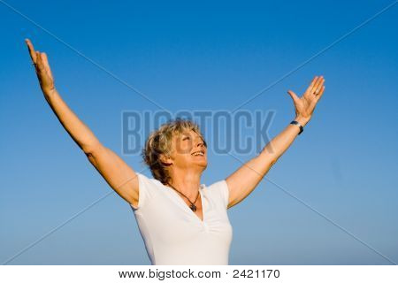 Happy Senior Woman Arms Raised With Joy