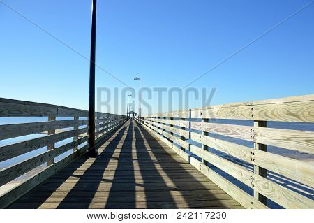 Wooden Pier Leading Into A Cloudless Sky